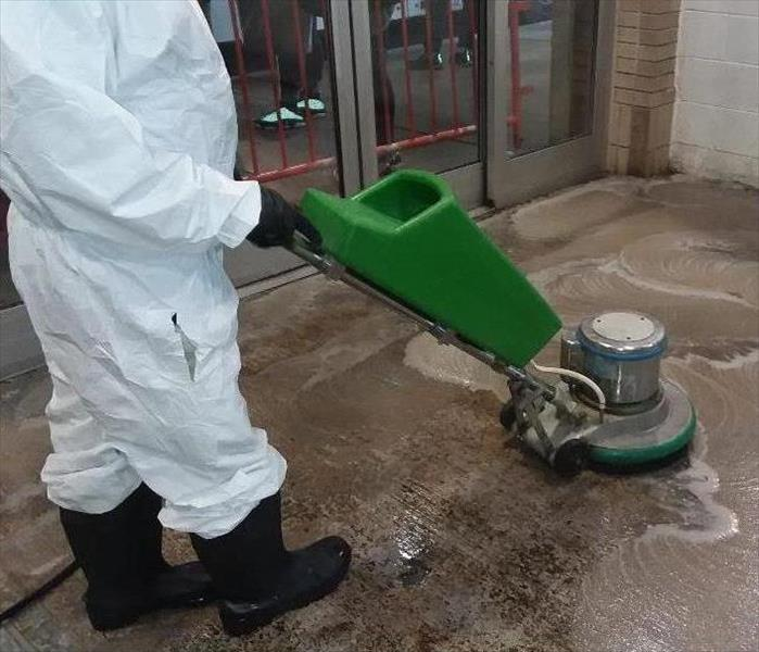SERVPRO Technician using equipment to clean the soot on the floor from fire damage.