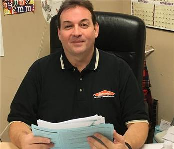 Steve McCauley sitting at his desk with papers in his hands