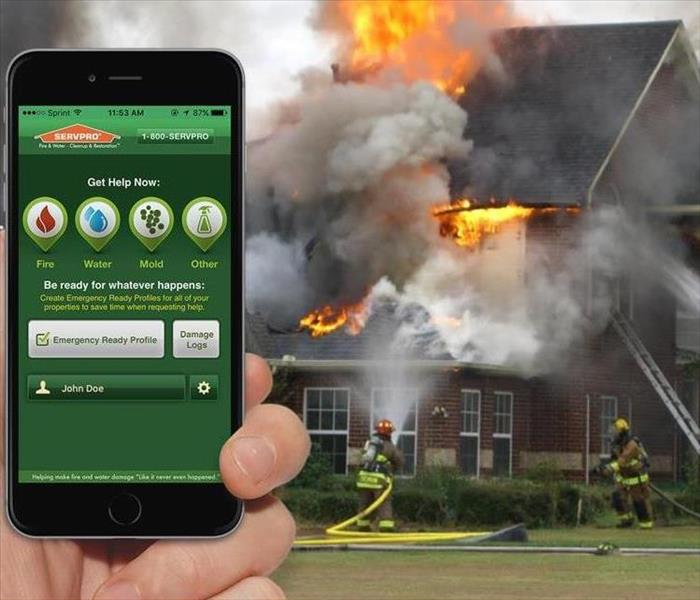 Home on fire with firemen putting out flames and hand holding a cell phone with the SERVPRO App displayed on it.