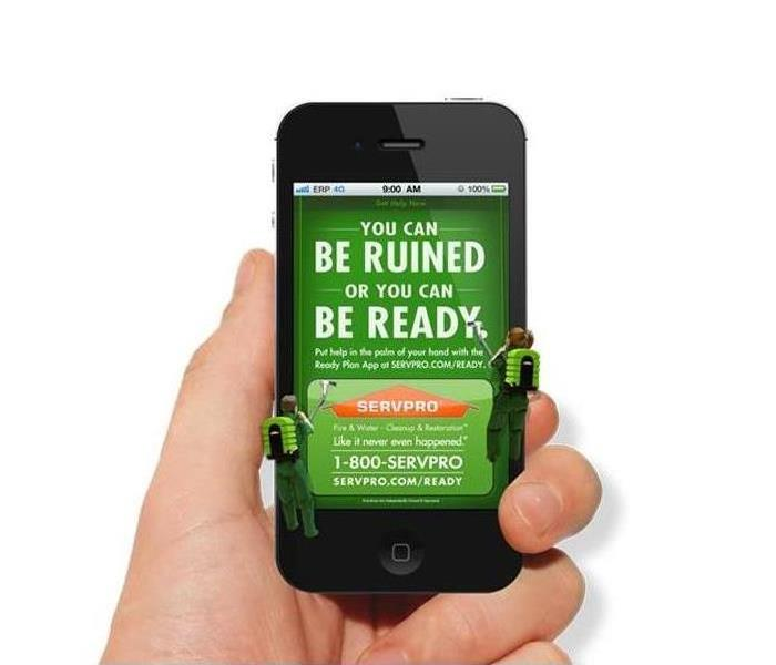Person holding cell phone with SERVPRO Ready App.