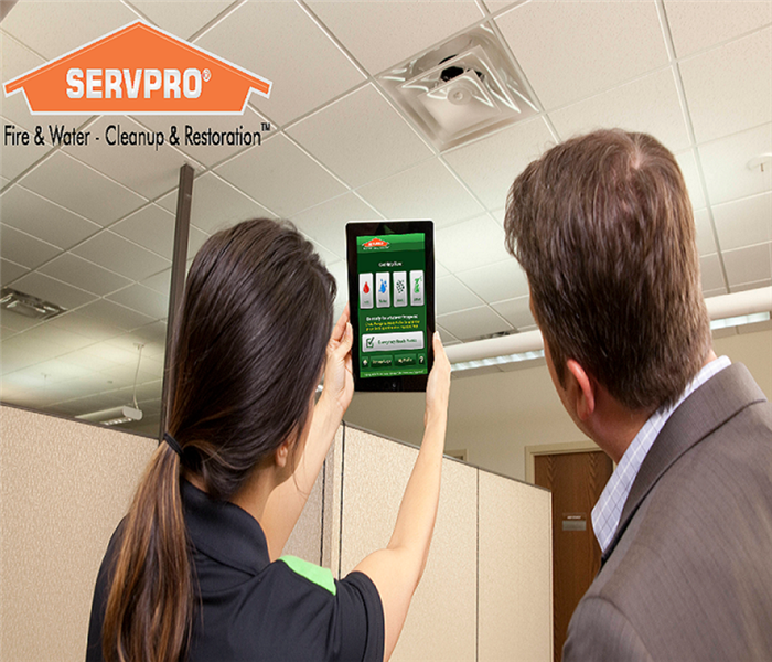 Business man looking at a SERVPRO technician holding up an Ipad with the SERVPRO Ready Application on the device