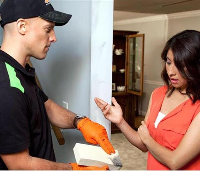A man dressed in a SERVPRO shirt showing a woman a sponge with mold on it.
