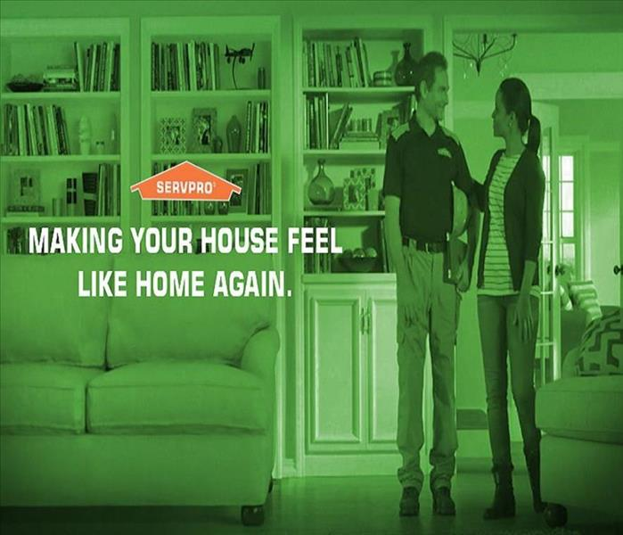 A man dressed in a SERVPRO shirt and woman standing together near a couch inside the family room of a house.