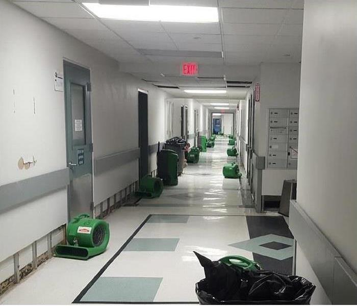 Image of a office hallway with SERVPRO equipment.