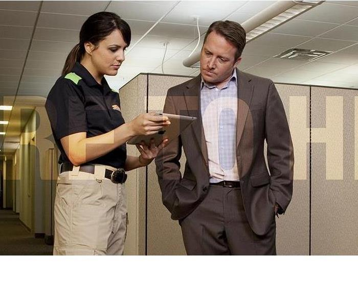 SERVPRO Technician and Business Owner talking in a corporate office